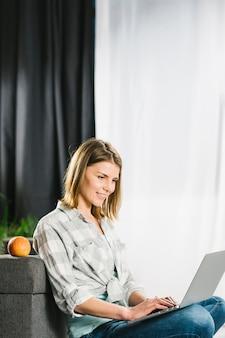 Hermosa mujer usando laptop cerca de sofá