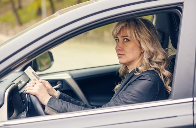 Una hermosa mujer en la ventanilla del automóvil muestra una licencia de conducir.