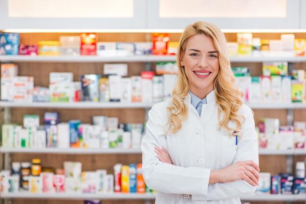 Hermosa mujer vestida con bata blanca de laboratorio trabajando en droguería.