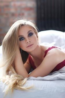 Hermosa mujer vestida con lencería sexy roja en la cama