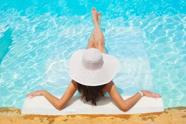 Hermosa mujer vestida con sombrero blanco y bikini acostada en una piscina