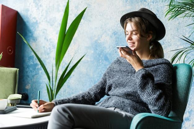 Hermosa mujer vestida con suéter y sombrero sentado en una silla en la mesa de café, hablando por teléfono móvil, elegante interior