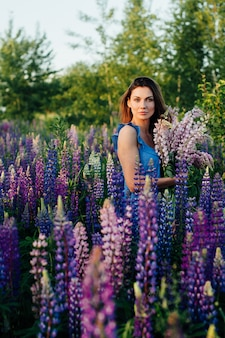 Hermosa mujer vestida con un vestido de flores lupines al atardecer