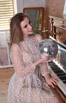 Hermosa mujer con un vestido beige sostiene una bola de discoteca en la mano y toca un piano retro