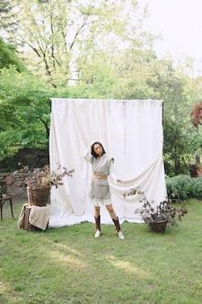 Hermosa mujer en vestido blanco y gris sentado en el suelo y mirando en el jardín.