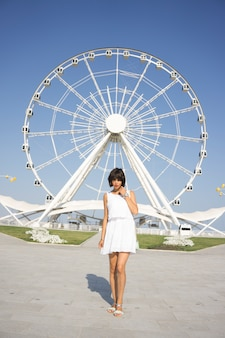 Hermosa mujer en vestido blanco de pie y mirando en el parque con noria