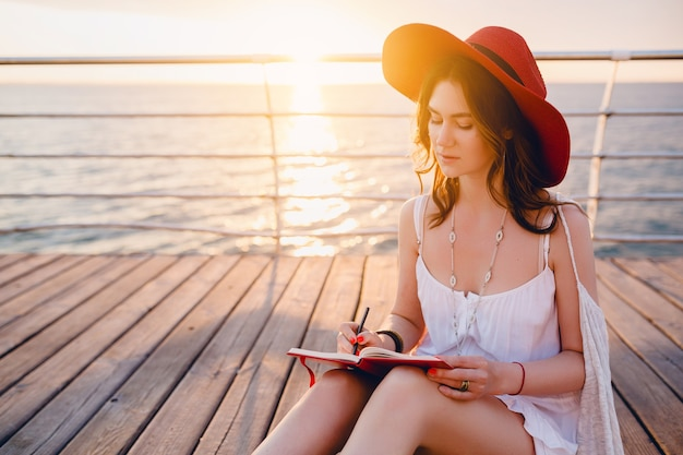 Hermosa mujer en vestido blanco sentada junto al mar en el amanecer pensando y haciendo notas en el libro diario