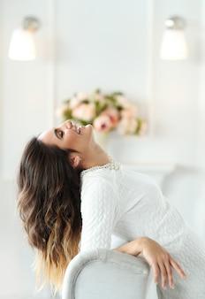 Hermosa mujer con vestido blanco y sentada en whithttps: //cdn-contributor.freepik.com/racool_studio/3949505/previews/626/d68i3607.jpge sillón