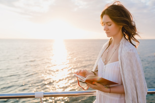 Hermosa mujer en vestido blanco de verano caminando por el mar al amanecer con libro diario en estado de ánimo romántico pensando y tomando notas