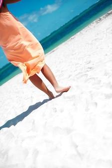 Hermosa mujer en vestido caminando cerca de la playa del océano en día de verano en arena blanca