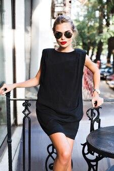 Hermosa mujer en vestido corto negro apoyado en la valla en la terraza. ella está mirando a la cámara.