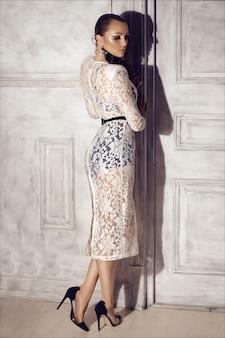 Hermosa mujer en vestido de encaje blanco y tacones altos con maquillaje de belleza y peinado.