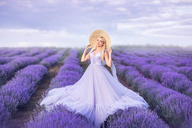 Hermosa mujer con un vestido largo morado sobre un fondo de lavanda. una niña en forma de hada y ninfa de flores.
