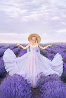 Hermosa mujer con un vestido largo sobre un fondo de lavanda. una niña en forma de hada y una ninfa de flores.