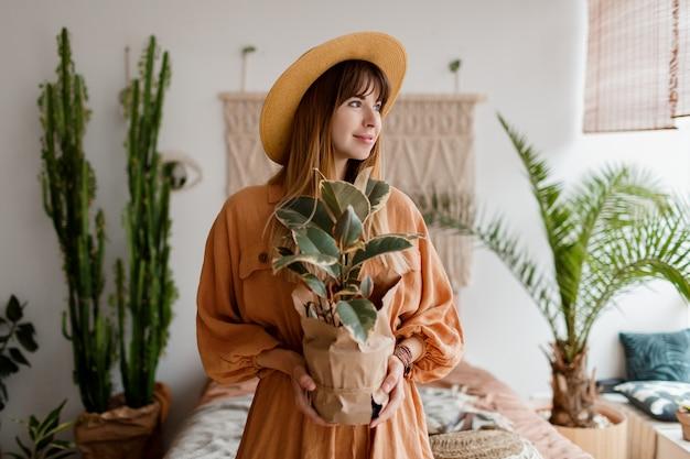 Hermosa mujer en vestido de lino y sombrero de paja posando en apartamento de estilo boho