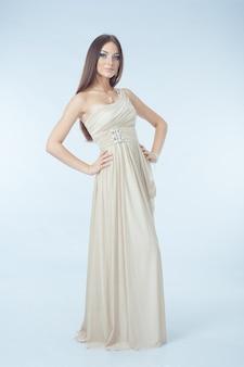 Hermosa mujer con vestido moderno posando en studio