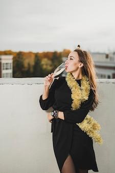 Hermosa mujer en vestido negro bebiendo champaña
