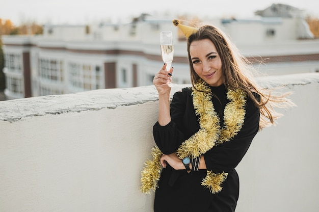 Hermosa mujer en vestido negro con una copa de champán