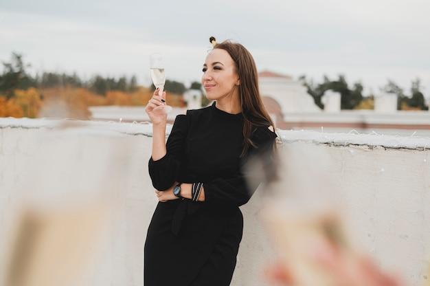 Hermosa mujer en vestido negro en el fondo de copas de champán borrosas