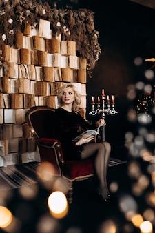 Hermosa mujer en vestido negro se sienta ante una pared de libros y decoración de navidad