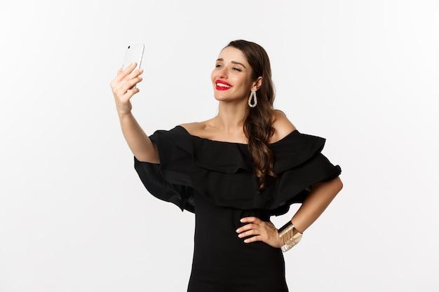 Hermosa mujer en vestido negro tomando selfie en fiesta, de pie sobre fondo blanco con smartphone.