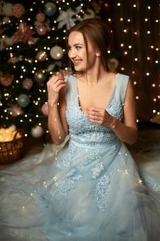 Hermosa mujer en un vestido de noche azul en el fondo de un árbol de navidad y guirnaldas
