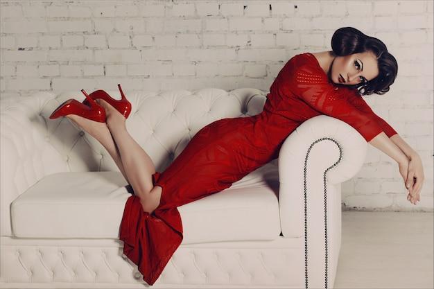 Hermosa mujer en vestido de noche largo rojo y tacones altos con maquillaje de belleza y peinado retro.