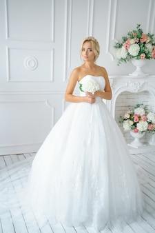 Hermosa mujer en un vestido de novia con un hermoso maquillaje y cabello