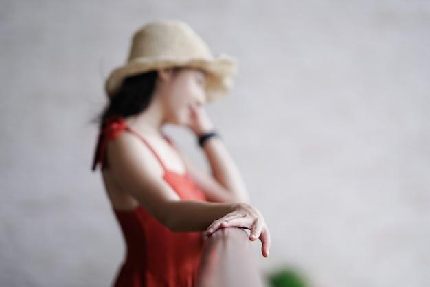 Hermosa mujer en vestido de pie en la mano de foco de balcón