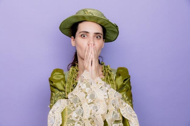 Hermosa mujer en vestido renacentista y sombrero conmocionado cubriendo la boca con las manos en azul
