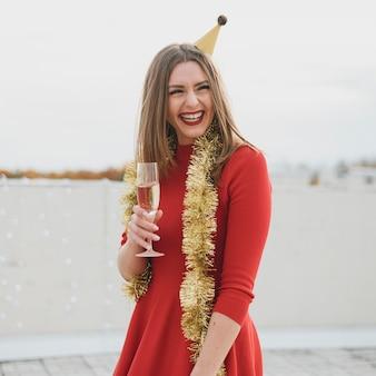 Hermosa mujer en vestido rojo divirtiéndose en una fiesta