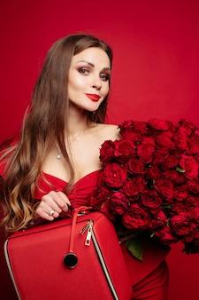Hermosa mujer en vestido rojo manteniendo ramo de rosas