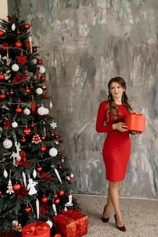 Hermosa mujer en vestido rojo plantea antes de rico árbol de navidad
