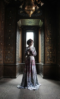 Hermosa mujer en vestido rosa posando en el palacio de lujo