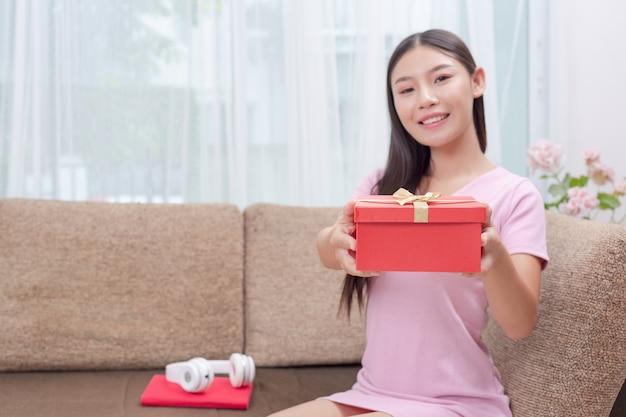 Hermosa mujer en vestido rosa, sentada en el sofá, abriendo una caja de regalo.