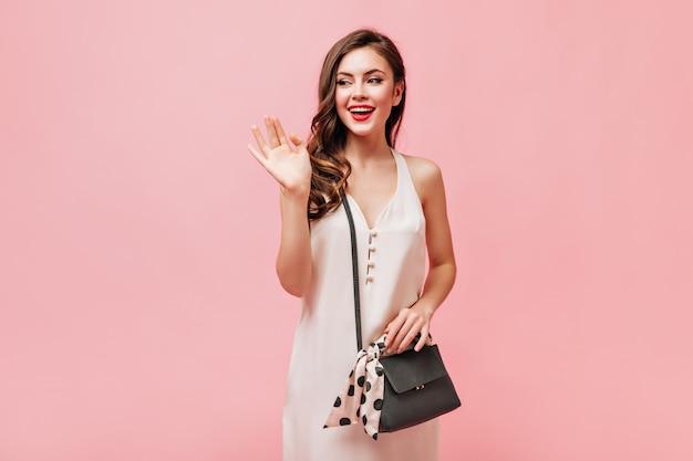 Hermosa mujer en vestido de seda agitando su mano y posando con bolso bandolera sobre fondo rosa.