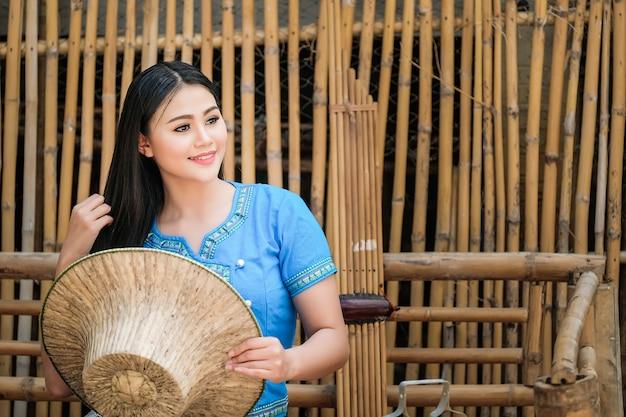Hermosa mujer con un vestido tradicional tailandés, azul en un ambiente rústico tailandés