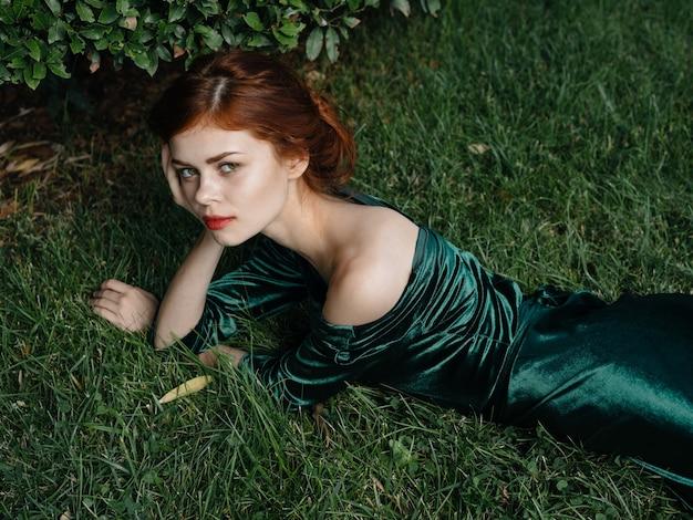 Hermosa mujer vestido verde césped arbusto aire fresco de lujo.