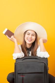 Hermosa mujer viajera es emocionante en pared amarilla