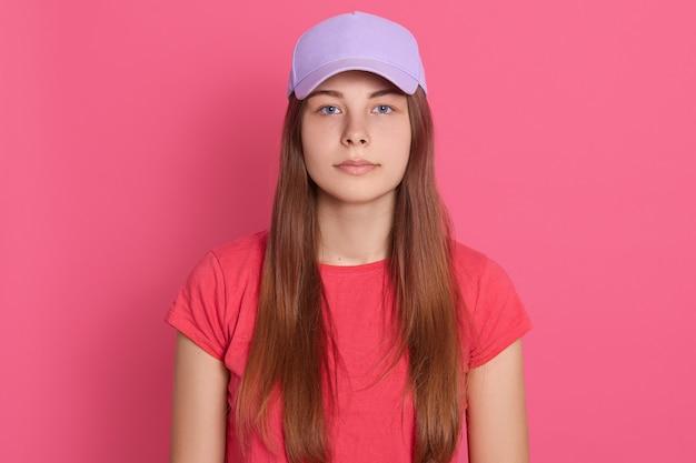 Hermosa mujer vistiendo gorra de béisbol y camiseta posando aislado sobre pared rosa con expresión seria en la cara, con el pelo largo y liso.