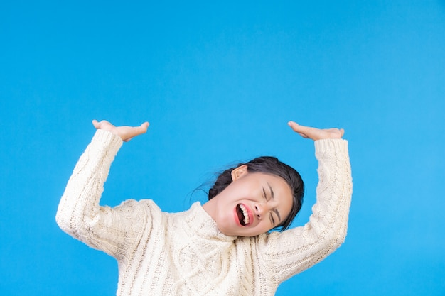 Hermosa mujer vistiendo una nueva alfombra blanca de manga larga, mostrando un gesto en un azul. comercio .