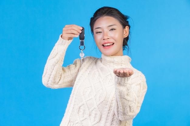 Hermosa mujer vistiendo una nueva alfombra blanca de manga larga, sosteniendo un llavero en la mano en un azul. trading s.
