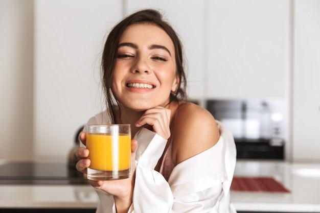 Hermosa mujer vistiendo ropa de seda sonriendo y bebiendo jugo de naranja en la cocina