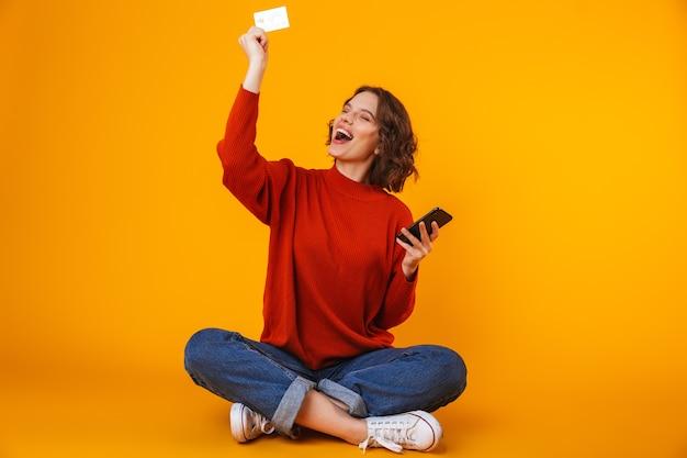 Hermosa mujer vistiendo un suéter con teléfono celular y tarjeta de crédito mientras está sentado en el piso aislado en amarillo