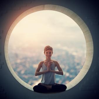 Hermosa mujer yogui en forma deportiva practica yoga asana padmasana - postura de loto en una ventana redonda