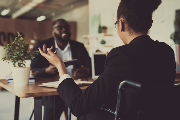 Hermosa mulata entrevistando a un hombre en la oficina.