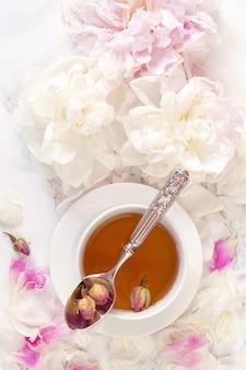 Hermosa naturaleza muerta con taza de té y peonías.
