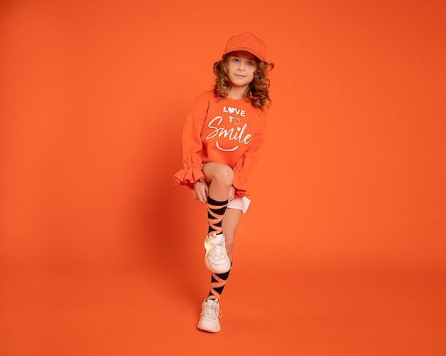 Hermosa niña de 6-7 años en gorra en zapatillas de deporte salta y baila sobre fondo naranja. fotografía publicitaria para estudio de danza con espacio de copia.