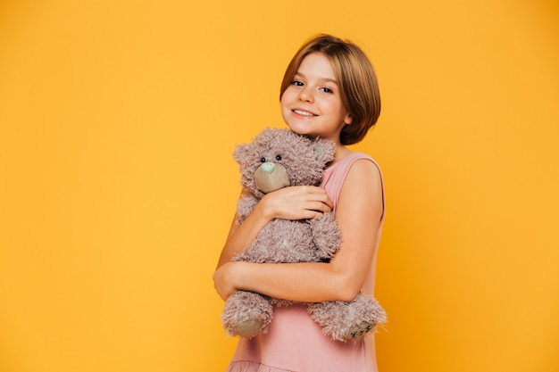 Hermosa niña abraza a su oso de peluche y sonriendo a la cámara