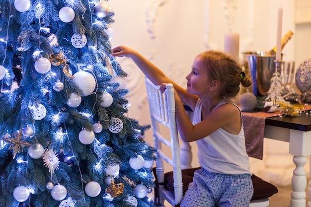 Hermosa niña en adornos navideños y esperando a santa